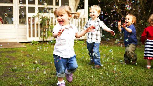 Niños pequeños jugando con burbujas