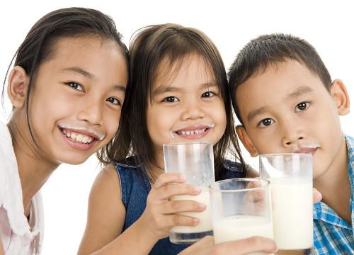 Niños beben leche felices
