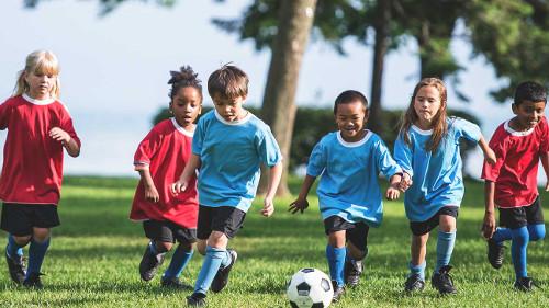 Niños y niñas juegan futbol